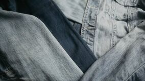 Different shades of blue denim fabric. Detail of several layers of jeans