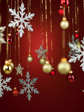 Different shaped shiny christmas decorations. Closeup of shiny christmas decorations hanging from golden threads on red background Stock Photos