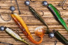 Different shapes, colors and weights of bait for catching large fish lie on a burnt wooden background royalty free stock images