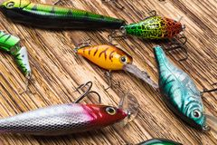 Different shapes, colors and weights of the bait in the form of fish for fishing lie on a burnt wooden background, close-up royalty free stock images