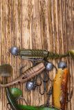 Different shapes, colors and weights of the bait in the form of fish for fishing lie on a burnt wooden background, on top there is. A place for your inscription royalty free stock photography