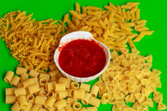 Different shapes of pasta with red sauce. Exposure of different shapes  of pasta with red sauce ready to cook Royalty Free Stock Photography