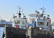 Different ships in one harbor. Tow boats, submarine and liner at harbor Royalty Free Stock Photo