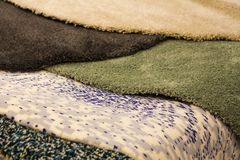 Different short wool rugs are colored in the overlap horizontally to the counter. Close up Stock Photography