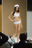 Different the show.  Lingrie Expo. Moscow. Young woman in a white bathing suit White Roses Flash Desire Stock Image