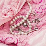 Different silver pear jewellery a. Nd closeup pearl on pink silk dress Stock Photo