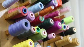 Different size and color threads in sewing studio stock video