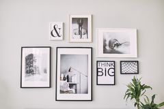 Different size framed photos hanging on the gray wall. Stylish framed photos on the wall. Modern interior stock photo
