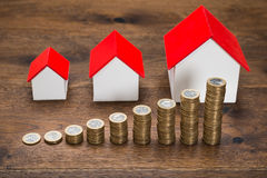 Different Size Houses With Coins Stock Images