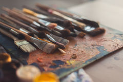 Different size paintbrush collection on an old palette with oil paint colors blend and a gouache set Royalty Free Stock Image