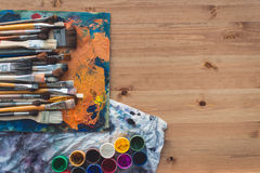 Different size paintbrush collection on an old palette with oil paint colors blend and a gouache set, top view picture. Royalty Free Stock Photo