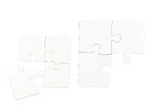 Different size pieces of white puzzle on a table Stock Photography