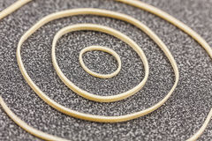 Different size rubber bands form a circular design on office desktop. Studio shot stock photos