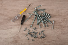 Different size screws and screwdrivers lay on table Stock Photography