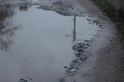 Different sized holes in the road. Different sized holes in the road filled with water Stock Images