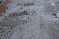 Different sized holes in the road. Different sized holes in the road filled with water Royalty Free Stock Images