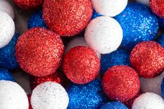 Different sized red white and blue glitter balls. Different sized ornamental red white and blue glitter balls in a random pattern close up full frame view for stock images