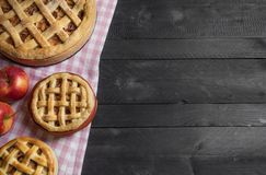 Different sizes apple pies on a rustic table. Above view with copy space stock image