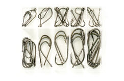 Different sizes of fishing hooks in plastic box isolated on whit Royalty Free Stock Photos