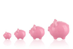 Different sizes of piggy banks. Saving money concept - Growing savings . Different sizes of piggy banks Stock Image
