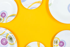 Different sizes plates frame, bright yellow background, copy space stock image