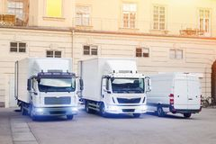 Different small and medium courier service  trucks and van at building courtyard. City delivery cargo shipping company vehilcles. Parked at street stock photography