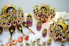 Different snack and canape on a table with Russian dolls Stock Image