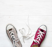 Different sneakers. Claret and grey sneakers laces tied in knot Royalty Free Stock Photography
