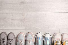Different sneakers on wooden floor, top view. With space for text stock photos