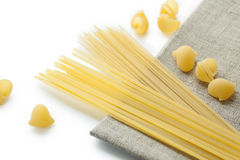 Different sort of macaroni shells and spaghetti on brown napkin. Different sort of raw italian macaroni shells and spaghetti on brown napkin, selective focus Royalty Free Stock Image