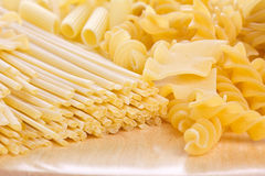 Different sort of macaroni on wooden board Stock Images