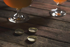 Different sorts of beer. Detail of two beer glasses with different sorts of beer placed on a rustic wooden table. Selective focus Royalty Free Stock Images