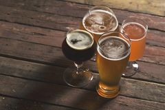 Different sorts of beer. Pale, dark, unfiltered pale and red fruit beer in four different beer glasses on a rustic wooden table. Selective focus Stock Images