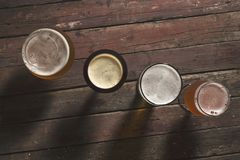 Different sorts of beer. Pale, dark, unfiltered pale and red fruit beer in four different beer glasses on a rustic wooden table. Selective focus royalty free stock image