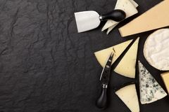 Different sorts of cheese. On dark slate background Stock Photo
