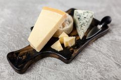 Different sorts of cheese. On dark slate background Royalty Free Stock Photography