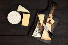 Different sorts of cheese. On dark slate background Stock Photos