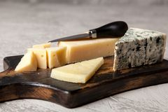 Different sorts of cheese. On dark slate background Stock Image