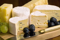 Different sorts of cheese. And grapes with cheese knife Royalty Free Stock Images