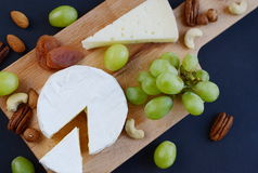 Different sorts of cheese with nuts, dried fruits and grapes on wooden plate Stock Image