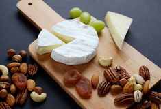 Different sorts of cheese with nuts, dried fruits and grapes on wooden plate Stock Photo