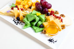 Different sorts of cheese, sliced, red grapes, walnuts, honey in a bowl, red currant, green cheese, wooden stand Stock Photo