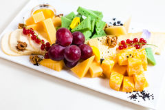 Different sorts of cheese, sliced, red grapes, walnuts, honey in a bowl, red currant, green cheese, wooden stand Stock Image