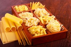Different sorts of pasta. On brown wooden table Stock Images