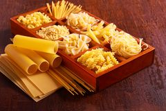 Different sorts of pasta. On brown wooden table Stock Photo