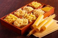 Different sorts of pasta. On brown wooden table Royalty Free Stock Photography