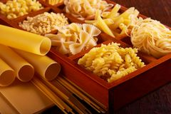 Different sorts of pasta. On brown wooden table Royalty Free Stock Photos
