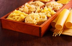 Different sorts of pasta. On brown wooden table Stock Photography