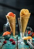 Different sorts of sorbet in waffle cones on a wooden table. Different sorts of sorbet in waffle cones on a wooden table royalty free stock photo
