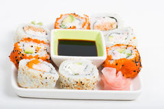 Different sorts of sushi on the plate. Different sorts of sushi rolls with soy sauce on the plate stock photos